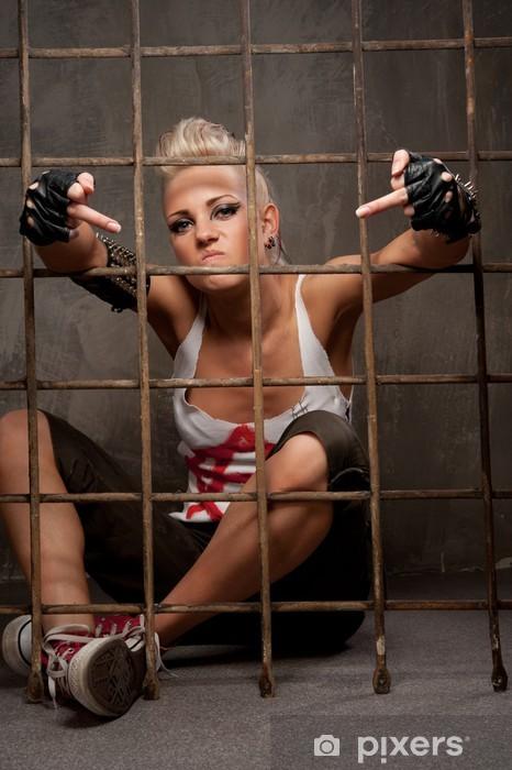 Vinylová fototapeta Punk dívka za mřížemi zobrazující hrubé gesto. - Vinylová fototapeta