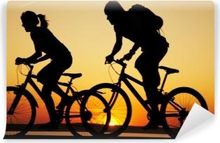 Abwaschbare Fototapete Junges Paar auf Fahrrädern bei Sonnenuntergang.