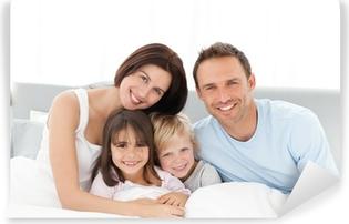Abwaschbare Fototapete Portrait einer glücklichen Familie auf dem Bett sitzend