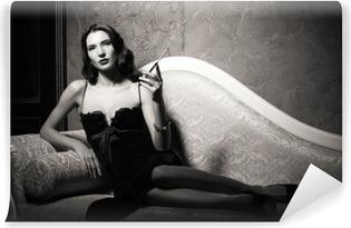 Afwasbaar Fotobehang Film noir stijl: elegante jonge vrouw liggend op de bank en het roken van sigaretten. Zwart en wit