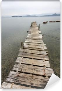 Afwasbaar Fotobehang Kijkt uit over een desolate peer en een boot.