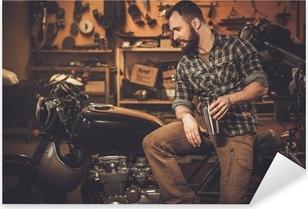 Pixerstick Aufkleber Mann und Vintage-Stil Café-Rennläufer-Motorrad in der Garage