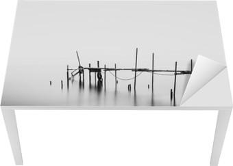 En lang eksponering af en ødelagt pier i midten af havet. Behandlet i B & W. Bord og skrivbordfiner