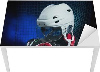 Bord- og skrivebordsklistremerke Hockeyhansker, hjelm og pinne lå på is.