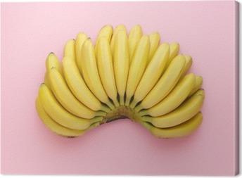 Canvas Bovenaanzicht van rijpe bananen op een heldere roze achtergrond. Minimalistische stijl.