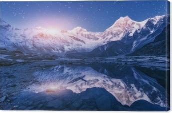 Canvas Nachtscène met Himalayan-bergen en bergmeer bij sterrige nacht in Nepal. landschap met hoge rotsen met besneeuwde top en hemel met sterren en maan weerspiegeld in het water. maansopgang mooie manaslu