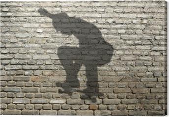 Canvas Ombre de skate-boarder sur mur de briques