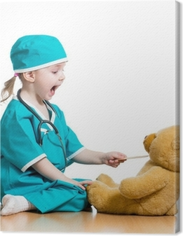 Adorable child dressed as doctor playing with toy over white Canvas Print