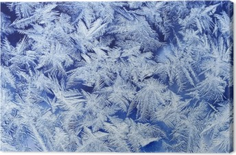 beautiful festive frosty pattern with white snowflakes on a blue background on glass Canvas Print