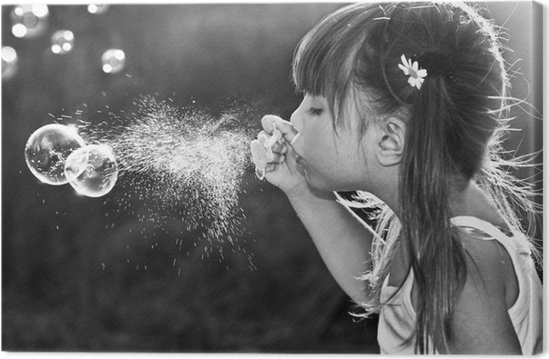 Black and white portrait of a little girl blowing soap bubbles canvas print