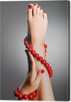 Closeup photo of a beautiful female feet with red pedicure Canvas Print