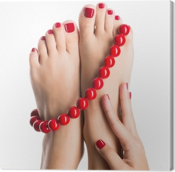 Closeup photo of a female feet with beautiful red pedicure Canvas Print