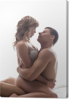 Couple playful lovers sit in bed - sexual games Canvas Print