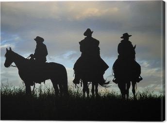 Cowboys on horseback on a Montana ridge at dawn Canvas Print