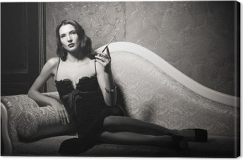 Film noir style: elegant young woman lying on sofa and smoking cigarette. Black and white Canvas Print