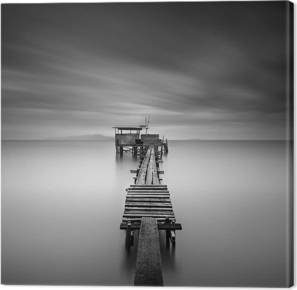 Fine art image of wooden fishing jetty at beach in black and white long exposure shot with motion blur canvas print