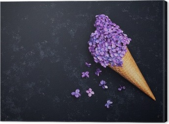 Ice cream of lilac flowers in waffle cone on black background from above, beautiful floral arrangement, vintage color, flat lay styling Canvas Print