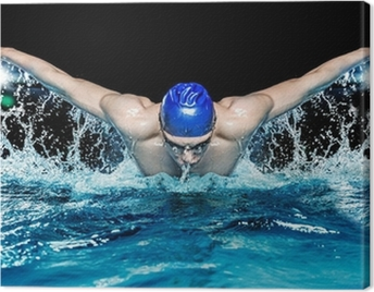 Muscular young man in blue cap in swimming pool Canvas Print