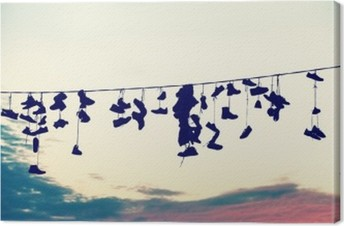 Retro stylized silhouettes of shoes hanging on cable at sunset, teenage rebellion concept. Canvas Print