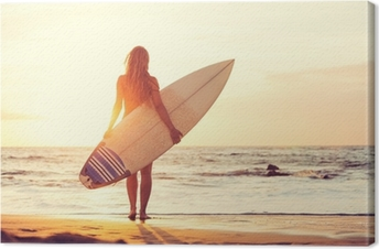 Surfer girl on the beach at sunset Canvas Print