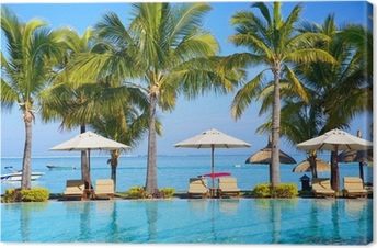 Swimming pool with umbrellas on beach in Mauritius Canvas Print
