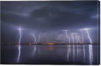 Thunderstorm and lightnings in night over a lake with reflaction Canvas Print