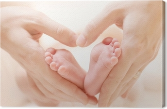 Tiny Newborn Baby's feet on female Heart Shaped hands closeup Canvas Print