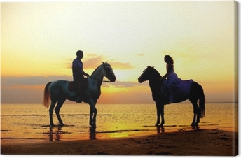 Two riders on horseback at sunset on the beach. Lovers ride hors Canvas Print