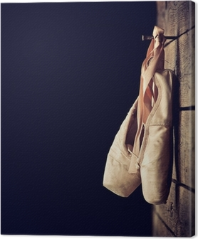 Used ballet shoes hanging on wooden background Canvas Print
