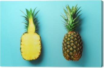 Whole pineapple and half sliced fruit on blue background. Top View. Copy Space. Bright pineapples pattern for minimal style. Pop art design, creative concept Canvas Print