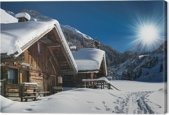 winter ski chalet and cabin in snow mountain landscape in tyrol Canvas Print
