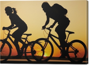 Young couple riding bicycles at sunset Canvas Print