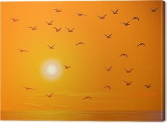 Canvas Vliegende vogels tegen oranje zonsondergang.
