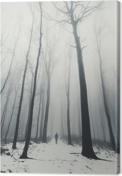 Canvastavla Man i skog med höga träd på vintern - Landskap