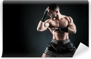 Carta da Parati in Vinile Sportivo kick boxer intenso ritratto contro sfondo nero.