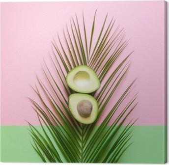 Cuadro en Lienzo Aguacate maduro en hoja de palma en un fondo coloreado. concepto restringido