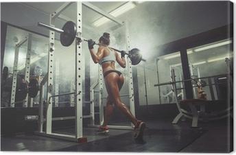 Cuadro en Lienzo Muchacha atractiva joven en el gimnasio haciendo sentadillas en el fondo de humo