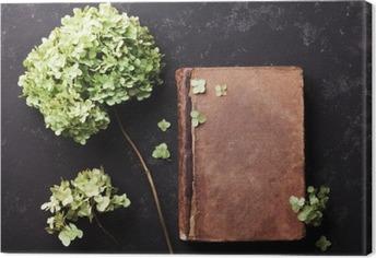 Cuadro en Lienzo Todavía vida con el libro viejo y flores secas hortensias en la mesa de la vendimia vista superior negro. estilo aplanada.