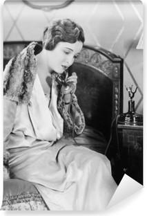 Vinil Duvar Resmi Genç kadın telefonla konuşan, yatak odasında yatağın üzerine oturan