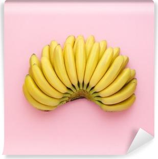Vinyl Fotobehang Bovenaanzicht van rijpe bananen op een heldere roze achtergrond. Minimalistische stijl.