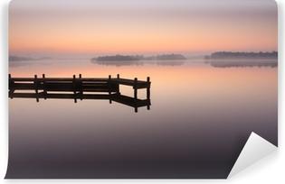 Vinyl Fotobehang Jetty tijdens een rustige, mistige zonsopgang op een meer.