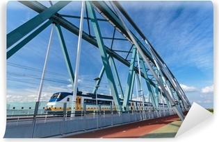 Vinyl Fotobehang Nederlandse trein passeren van een brug in Nijmegen