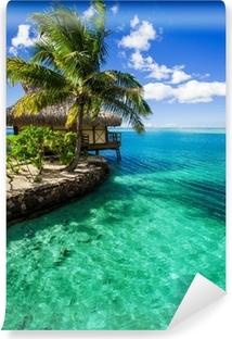 Vinyl Fotobehang Tropische villa en palmboom naast groene lagune