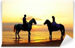 Vinyl Fotobehang Twee ruiters te paard bij zonsondergang op het strand. Lovers rijden hors
