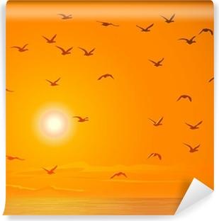 Vinyl Fotobehang Vliegende vogels tegen oranje zonsondergang.