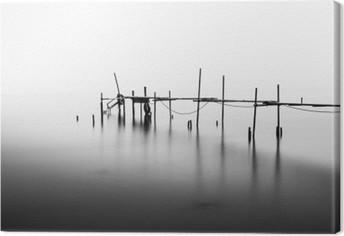 En lang eksponering af en ødelagt pier i midten af havet. Behandlet i B & W. Fotolærred