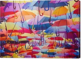 Farverige paraplyer hængende over gaden Fotolærred