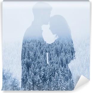 Fotomural Estándar Amor en invierno, silueta de la pareja en el fondo del bosque, doble exposición