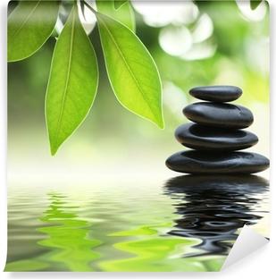 Fotomural Autoadhesivo Pirámide de piedras zen en la superficie del agua, las hojas verdes sobre ella