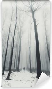 Fotomural Estándar El hombre en el bosque con árboles altos en invierno